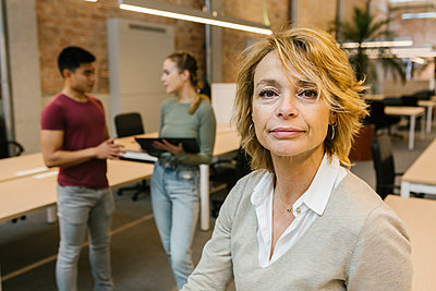 Mature businesswoman with blond hair with male and female coworkers in background at office - p300m2282653 by Xavier Lorenzo