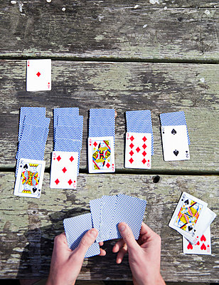 Man playing cards - p956m1044292 by Anna Quinn