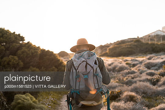 Italy, Sardinia, back view of hiker with hat and backpack - p300m1581523 von VITTA GALLERY