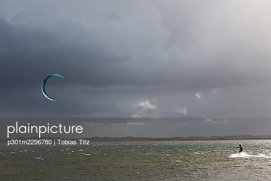 Kite boarder on ocean below stormy cloudy sky - p301m2296780 by Tobias Titz