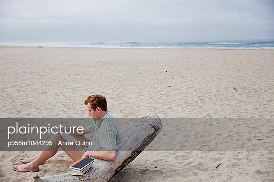 Man reading on beach - p956m1044295 by Anna Quinn