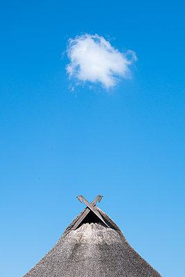 Reetgedecktes Haus mit Wolke - p1079m2133124 von Ulrich Mertens