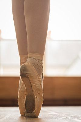 Ballerina dancing on wooden floor in dance studio - p1315m2017671 by Wavebreak