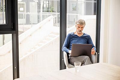 Mature man sitting in his office, using laptop - p300m1588139 von Jo Kirchherr
