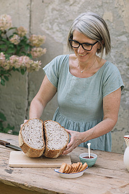 Smiling woman with halved bread at table - p300m2281436 by Alberto Bogo