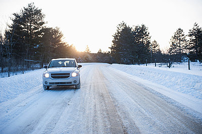 Car driving along road in snow - p924m836528f by Hugh Whitaker