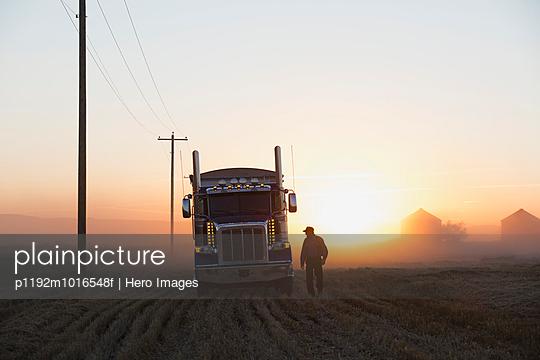 Truck driver near semi-truck in rural field