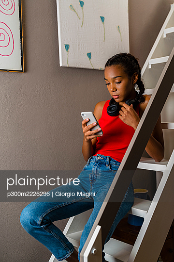 Teenage girl using smart phone while sitting on ladder at home - p300m2226296 by Giorgio Magini