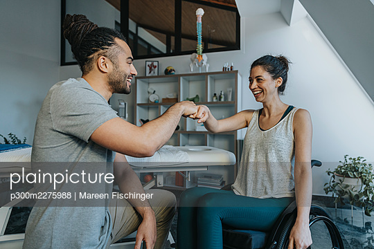 Happy female patient and physiotherapist giving fist bump in medical practice - p300m2275988 by Mareen Fischinger