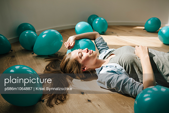 Young woman in new apartment with balloons - p586m1064887 by Kniel Synnatzschke