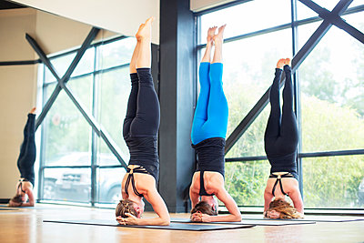 Friends practicing headstand pose in yoga class - p1166m1209746 by Cavan Images