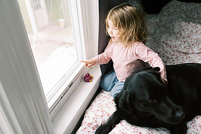 A little girl and her black Labrador. - p1166m2157454 by Cavan Images