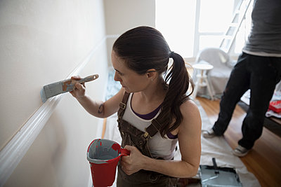 Focused young woman painting above chair rail, DIY - p1192m1560030 by Hero Images