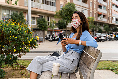 Woman looking away with smart phone while sitting on bench in city during COVID-19 - p300m2224919 by VITTA GALLERY