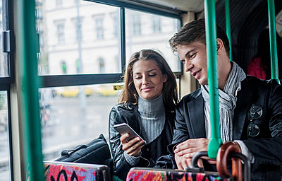 Smiling female and male colleagues using smart phone while commuting through bus - p300m2240026 by LOUIS CHRISTIAN