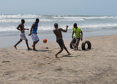 akrikanische Teenager spielen Fussball am Strand - p390m1590466 von Frank Herfort