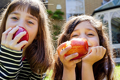 Girls eating apples outdoors - p42916568f by Axel Bernstorff