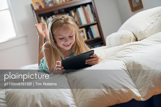 A young girl sitting on her bed using a digital tablet.  - p1100m876132f by Tim Robbins