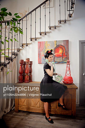 Woman in black dress talking with old phone, portrait - p1105m2244896 by Virginie Plauchut