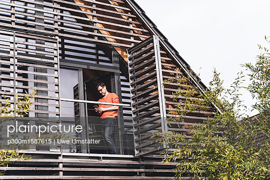 Man standing on balcony of his house looking at smartphone - p300m1587615 von Uwe Umstätter