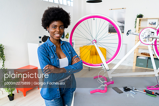 Smiling woman with arms crossed standing by bicycle at home - p300m2275899 by Giorgio Fochesato