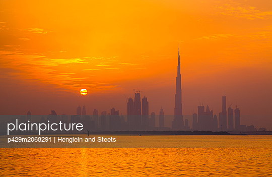 Orange glow of sky reflected in sea, Dubai, UAE - p429m2068291 by Henglein and Steets