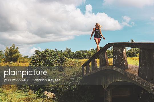 Philippines, Woman balances over a bridge - p986m2227408 by Friedrich Kayser