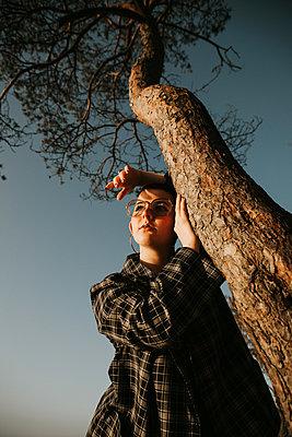 Girl leaning on tree, portrait - p1507m2263133 by Emma Grann