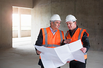 Two men with plan wearing safety vests talking in building under construction - p300m1460183 by Daniel Ingold