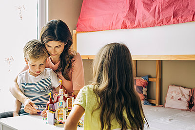 Mother with two children building up toy castle at home - p300m2029499 by Visualspectrum