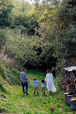 Rear view of family with two kids walking in the countryside - p300m2144423 by Sofie Delauw