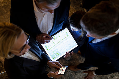 Top view of business people and girl looking at shining construction plan on tablet in office - p300m2156030 by Gustafsson