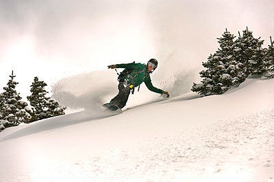 A snowboarder riding through powder.  - p343m1184694 by Rob Hammer