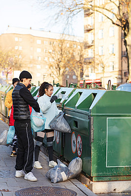 Young male and female environmentalists throwing waste in garbage can - p426m2213418 by Maskot