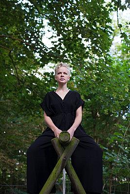 Blonde Frau sitzt auf Holzgestell - p906m1362770 von Wassily Zittel