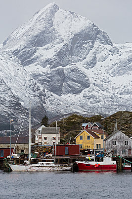 Fishing village and boats at waterfront below snowy, rugged mountains, Sund, Lofoten, Norway - p1023m1519823 by Agnieszka Olek
