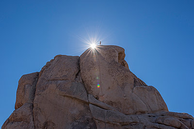 Low angle view of man standing on rock against clear blue sky - p1166m1532165 by Cavan Social