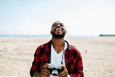 Laughing man holding an old-fashioned camera near the beach - p300m1188906 by Josep Rovirosa