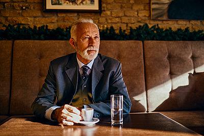 Portrait of elegant senior man sitting in a cafe - p300m1549419 by Zeljko Dangubic