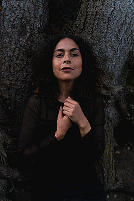Beautiful woman leaning on tree trunk - p300m2281771 by Francesco Morandini