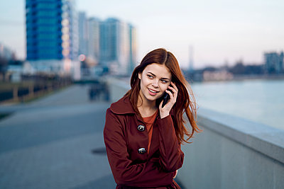 Caucasian woman talking on cell phone at waterfront - p555m1482009 by Dmitry Ageev