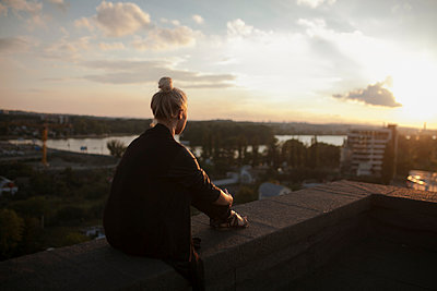 Caucasian woman on roof admiring scenic view of sunset - p555m1523076 by Mykhailo Lukashuk