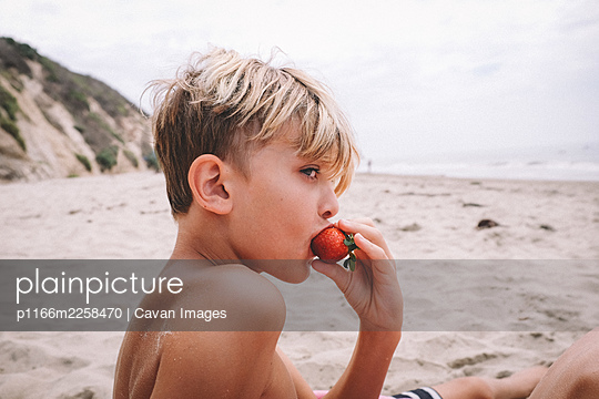 Boy Eating a Strawberry on a Sandy Beach in California - p1166m2258470 by Cavan Images