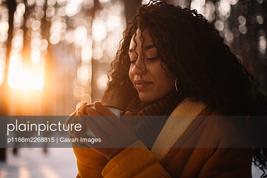 Young woman holding cup of tea standing at park in winter at sunset - p1166m2268815 by Cavan Images