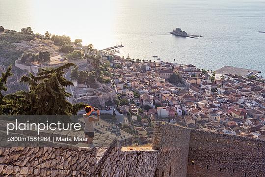 Greece, Peloponnese, Argolis, Nauplia, Argolic Gulf, woman photographing view to Bourtzi Castle - p300m1581264 von Maria Maar