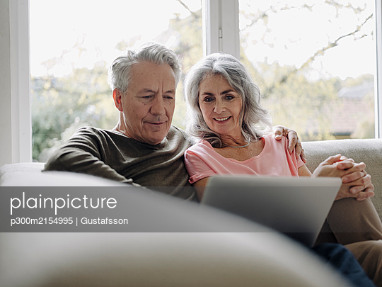 Senior couple with laptop relaxing on couch at home - p300m2154995 by Gustafsson