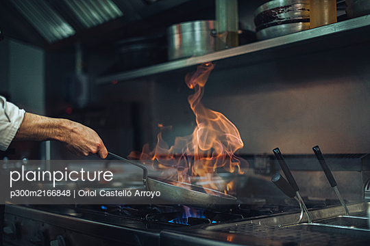 Chef preparing a flambe dish at gas stove in restaurant kitchen - p300m2166848 by Oriol Castelló Arroyo