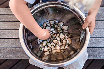 Toddler holding a large bowl of fresh shellfish - p1166m2130676 by Cavan Images