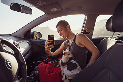 Happy person with two dogs on lap in car takes photos with phone spain - p1166m2236921 by Cavan Images