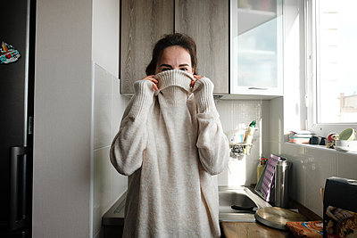 Woman covers her face with a sweater collar - p1363m2177572 by Valery Skurydin
